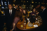 An after-work Christmas party at Coates Wine Bar on London Wall (street) gathers energy after nine o'clock pm at a table near the bar. A group of three girls sing along to a karaoke machine while one of the three sticks out her tongue towards her friend. They are each drinking glasses of white wine and two packets of Marlboro and one of Silk Cut cigarettes lies on the table surrounded by their handbags and other possessions including a camera. There are other people in the background including two men at the bar and a man on his own edging past with a cigarette in his right hand. It is a gloomy place to party with little artificial light to colour (color) the scene. The City of London has a resident population of under 10,000 but a daily working population of 311,000. The City of London is a geographically-small City within Greater London, England. The City as it is known, is the historic core of London from which, along with Westminster, the modern conurbation grew. The City's boundaries have remained constant since the Middle Ages but  it is now only a tiny part of Greater London. The City of London is a major financial centre, often referred to as just the City or as the Square Mile, as it is approximately one square mile (2.6 km) in area. London Bridge's history stretches back to the first crossing over Roman Londinium, close to this site and subsequent wooden and stone bridges have helped modern London become a financial success.