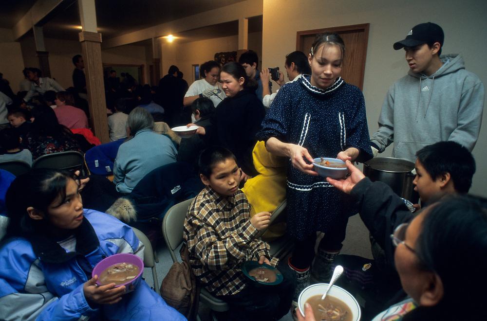 Alaska. Barrow. Sharing: Serving duck soup during Thanksgiving feast at church.