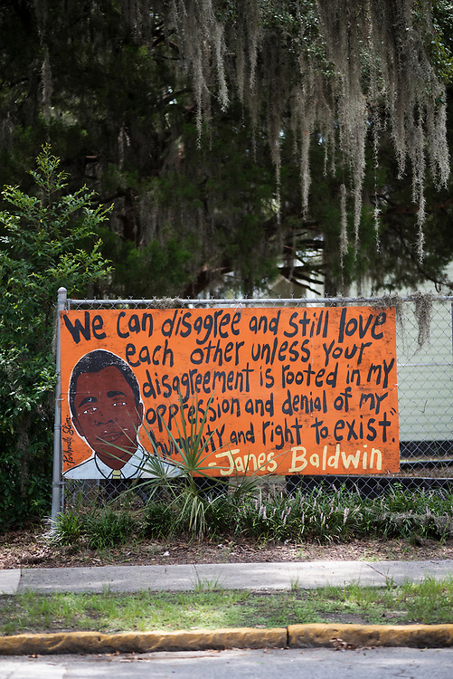 """Savannah, Georgia - July 30, 2021: A quote by James Baldwin, painted on a fence at the intersection of Bull and W 34th Streets ink Savannah, reads: """"We can disagree and sitll love each other unless your disagreement is rooted in my oppression and denial of my humanity and right to exist."""""""