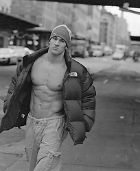 sexy muscular man with an open winter coat and no shirt in New York City