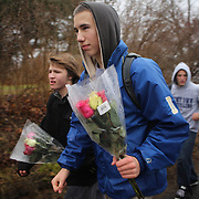 Teenage boys head to place flowers at the shrine set up at the school sign in Sandy Hook after the mass shootings at Sandy Hook Elementary School, Newtown, Connecticut, USA. 16th December 2012. Photo Tim Clayton