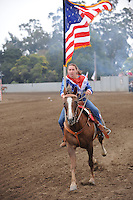 An early American flag enters the arena in the Pageant of Flags at the opening ceremonies for the 2013 California Rodeo Salinas on Thursday night.