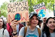 School Climate Strike, Parliament Square;London, England, UK. A young girl holds a sign saying Climate Action Now.