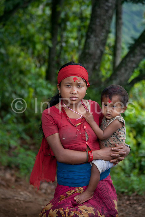 A young mother at a gathering high up in the mountains.  The Chepangs is an ethnic group which used to be nomadic. Only recently have the settled and their settlements are high up in the mountains. Only a few years ago they did not have any running water and had to bring up water from below but with the help pf Restless Development and their partner NGO Prayash Nepal they now have running clean water from springs diverted into resovoirs and the connected to taps inther settlement. This not only give them clean water to drink, it also improve hygiene dramatiaclly and improve health and it saves precious time for the women who now spend the 4 hours it used to take getting water growing healhty vegetables.