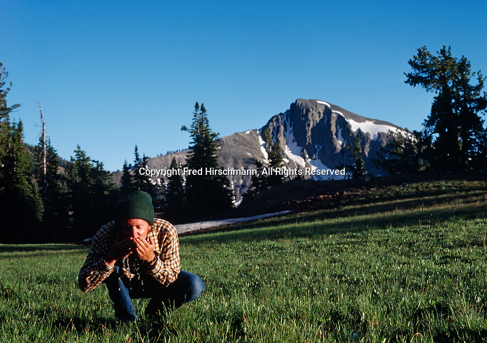 Frank Balthis drinking pure water from an alpine creek, Mount Doane of the Absaroka Mountains in the background, Yellowstone National Park, Wyoming.
