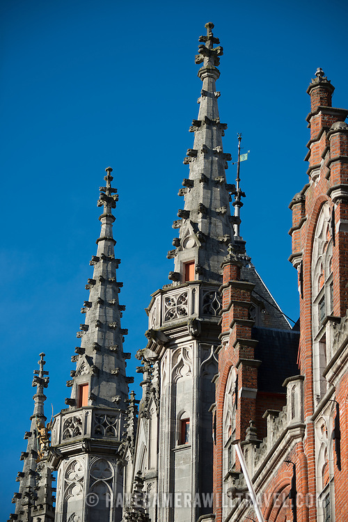 Spires of Gothic architecture rise up above the Provincial Court building on the Markt in the historic center of Bruges, Belgium.