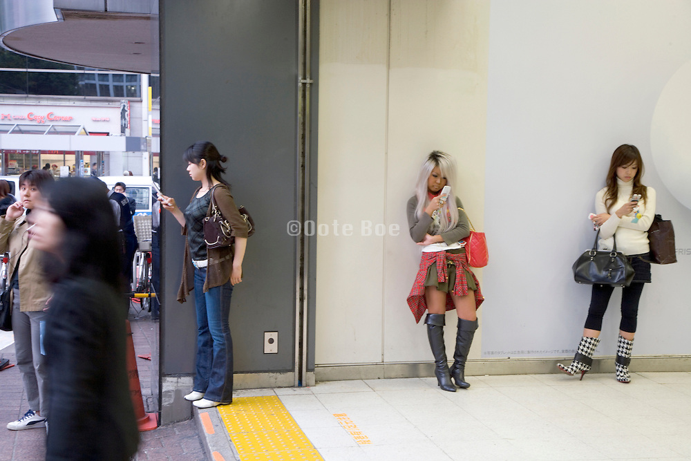 girls waiting outside Shibuya train station for there friends to arrive Tokyo Japan