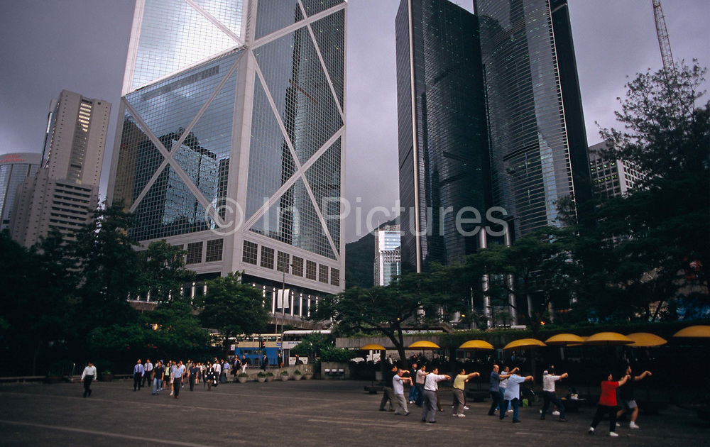 """On the very last day of British rule over its Hong Kong colony, we see two groups representing this colonial territory's population. Commuters walk through Chater Garden about to pass another group of older exercise class. Towering above them all is the Bank of China skyscraper, then the tallest building in Asia, As the last hours tick away before the transfer of sovereignty of Hong Kong from the United Kingdom to the Peoples Republic of China (PRC), often referred to as """"The Handover"""" on June 30, 1997. Midnight of that day signified the end of British rule and the transfer of legal and financial authority back to China. Almost 7 million people call a territory of 1100 sq km home, squeezing onto only 10% of the available land space. This is a metropolis of high population density and one of the world's economic powerhouses."""