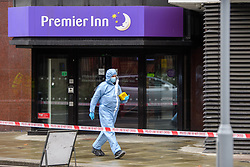 © Licensed to London News Pictures. 21/08/2021. London, UK. A forensic investigator walks past a Premier Inn hotel at the scene of a fatal stabbing in Kingston. Police were called to a disturbance on Clarence Street at 03:45BST where they found a 22-year-old male with a stab injury to the chest, he was taken to hospital by London Ambulance Service where he was pronounced dead. An 18-year-old male was arrested at the scene on suspicion of murder.Photo credit: Peter Manning/LNP