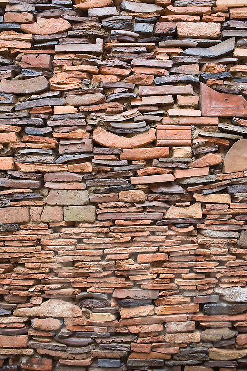 Color film photograph of brick wall detail in Tho Ha Village, a craft village specialized in making rice paper cakes with a history of pottery ware production, Hanoi outskirts, Vietnam, Southeast Asia