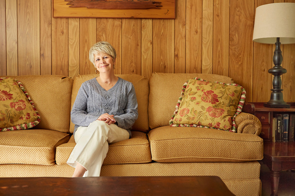 Portrait photograph of smiling senior lady sitting on yellow sofa inside home