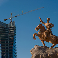 A crane atop a new high rise building in Ulaanbaatar towers over a statue of Damdin Sukhbaatar, who liberated Mongolia from China in 1922.