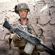 """Location:<br /> Patrol Base Fires, Sangin District, Helmand Province, Afghanistan<br /> <br /> Unit: <br /> 3rd Squad, 1st Platoon, Bravo Company, 1st Battalion, 5th Marines<br /> <br /> Name and Rank: Lance Corporal David James Richvalsky<br /> <br /> Age: 19<br /> <br /> Hometown: Waialua, Hawaii<br /> <br /> Why did you join the Marine Corps?<br /> <br /> """"I joined the Marine Corps because I wanted to get off the island of Hawaii. I was slightly patriotic, and . . . I don't know, that's really the only reason I had. . . . I joined the Marine Corps out of all the other branches because I wanted to fight.""""<br /> <br /> Tell me about all of the weight you carry as a machine gunner:<br /> <br /> """"I carry obviously an M 240-B Machingun, and it weighs 27.1 pounds. And I carry 500 rounds for it on my body, but in the squad we carry eight hundred. A hundred rounds weighs 7.7 pounds, so if you do the math it adds up. I also carry a night optic for it, a 17 Charlie. It's not very heavy but it adds up too. I also carry PVS-14s which is like night vision, and I also carry about eight waters.""""<br /> <br /> """"I carry 35 pounds in rounds, 27 pounds in gun . . . I probably carry about maybe 60-65 pounds worth of gun gear only, not counting my flak and my water and all that shit.""""<br /> <br /> What does it do to your body?<br /> <br /> """"It feels like I'm an old man, like I'm just gonna fall apart.""""<br /> <br /> """"It's just what the Marine Corps does, they just break you down in boot camp. Like, they'll never really build you up.""""<br /> <br /> Describe your living conditions:<br /> <br /> """"I live in a fucking mud hut. It's just about three feet thick walls of mud, the hajjis live in. And right now it's actually pretty dirty just because I've been disgusting and not cleaned it, and I got fleas because of the fucking chickens that run around.""""<br /> <br /> What is your role as a machine gunner during a firefight?<br /> <br /> """"Well, I always like doing my job when I'm shootin', 'cause"""