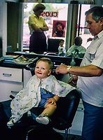 Fourteen month old boy getting his first haircut at Rocco's Barber Shop in Danbury, Connecticut USA. His mother looks on in the background.