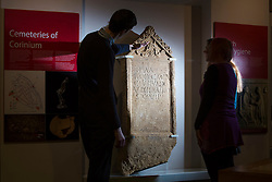 """© Licensed to London News Pictures 25/01/2016, Cirencester, UK. Collections officer James Harris (L) looks at a unique Roman tombstone, found in February 2015, here on display for the first time at Corinium Museum in Cirencester. The tombstone was found near skeletal remains thought to belong to the person named on its inscription, making the discovery unique. After being found during excavation works on a fomer site of a garage, archaeologists said they believed it marked the grave of a 27-year-old woman called Bodica. Other theories point to it possibly belonging to a couple - as skeletal remains of women were found nearby.<br /> The inscription reads """"To the shades of the dead, Bodicacia spouse lived 27 years"""". Photo Credit : Stephen Shepherd/LNP"""