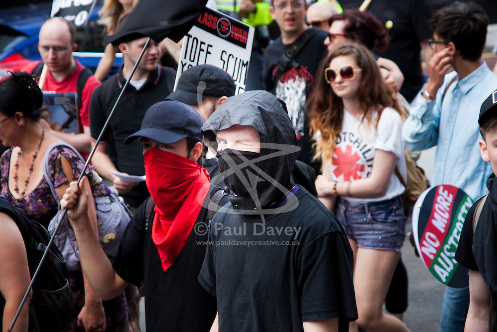 London, June 21st 2014. An anarchist winks for the camera as thousands march against austerity in London.