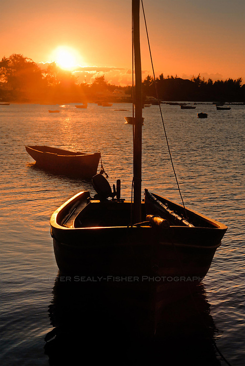 The sun sets over a bay of resting fishing boats on the East side of the island of Mauritius.