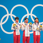 TOKYO, JAPAN - JULY 29: The world record breaking China team of Junxuan Yang, Yufei Zhang, Bingjie Li and <br />  Muhan Tang on the podium with their gold medals watched by Katie Ledecky of the United States after their gold medal win in the 4x 200m relay for women during the Swimming Finals at the Tokyo Aquatic Centre at the Tokyo 2020 Summer Olympic Games on July 29, 2021 in Tokyo, Japan. (Photo by Tim Clayton/Corbis via Getty Images)