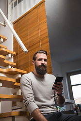 Portrait of young man holding cell phone