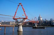 A 1999 landscape showing the construction of the new Millennium Bridge over the river Thames, opposite St. Paul's Cathedral in the City, on 16th February 1999, in London, England. The £18.2m Millennium Bridge (a Thames crossing linking the City of London at St. Paul's Cathedral with the Tate Modern Gallery at Bankside) was London's newest river crossing for 100-plus years and coincided with the Millennium, it was hurriedly finished and opened to the public on 10 June 2000 when an estimated 100,000 people crossed it to discover the structure oscillated so much that it was forced to close 2 days later. Over the next 18 months designers added dampeners to stop its wobble but it already symbolised what was embarrassing and failing in British pride. Now the British Standard code of bridge loading has been updated to cover the swaying phenomenon, referred to as Synchronous Lateral Excitation. (Photo by Richard Baker / In Pictures via Getty Images)