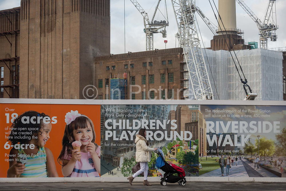 A mother and child in a push-chair walks past on-going construction work in Battersea, surrounding Battersea Power Station, on 22 January 2018, in south London, England.