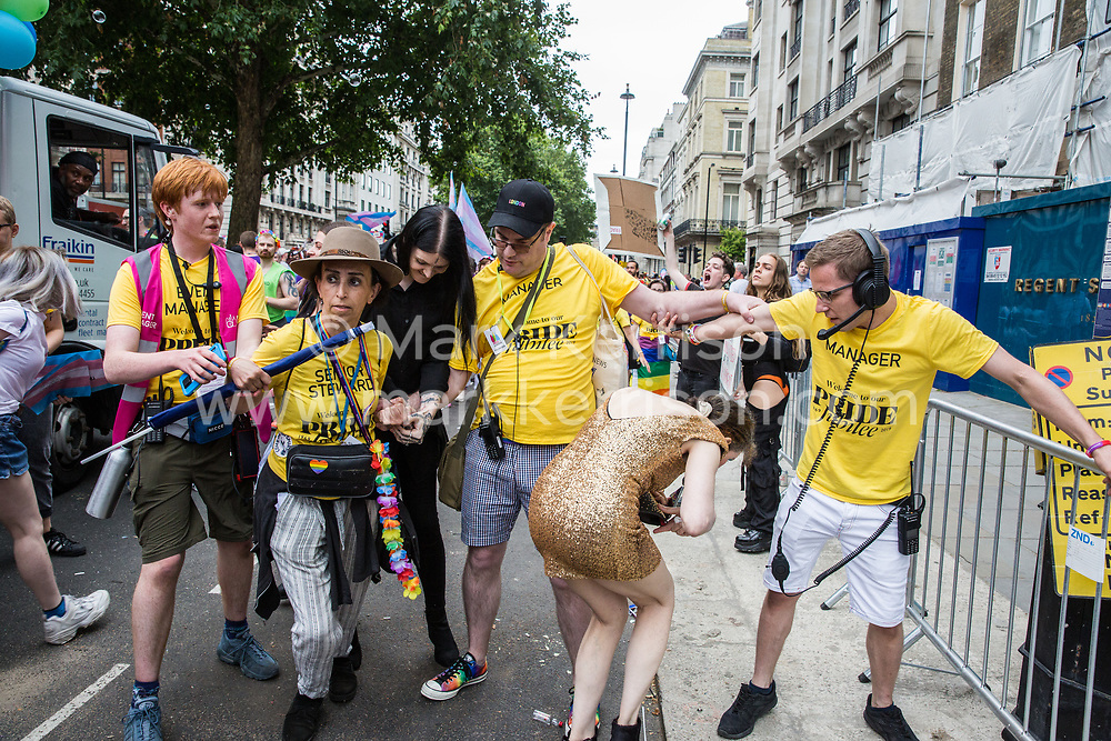 London, UK. 6 July, 2019. Pride in London stewards try to prevent activists from Lesbians and Gays Support The Migrants, African Rainbow Family, the Outside Project, Micro Rainbow and other LGBT+ groups from joining the Pride in London parade in solidarity with those for whom Pride in London is inaccessible and in protest against the corporatisation of Pride in London.