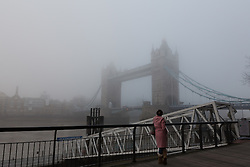© Licensed to London News Pictures. 17/12/2016. LONDON, UK.  A woman looks at Tower Bridge during foggy weather this morning. London and the River Thames was shrouded in thick fog this morning.  Photo credit: Vickie Flores/LNP