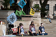 Protesters meditating at Extinction Rebellion demonstration on 4th September 2020 in London, United Kingdom. With government resitting after summer recess, the climate action group has organised two weeks of events, protest and disruption across the capital. Extinction Rebellion is a climate change group started in 2018 and has gained a huge following of people committed to peaceful protests. These protests are highlighting that the government is not doing enough to avoid catastrophic climate change and to demand the government take radical action to save the planet.
