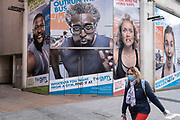 As numbers of Covid-19 cases in Birmingham have dramatically risen in the past weeks, increased lockdown measures are in place for Birmingham and other areas of the West Midlands, a woman wearing a face mask passes a large advertising hoarding for a gym in the city centre on 7th October 2020 in Birmingham, United Kingdom. With financial difficulties for many businesses, and the country in recession, the downturn in the economy has left forced many shops to close down, leaving high streets in the UK struggling.