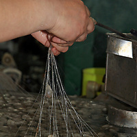 Asia, China, Suzhou. Pulling threads from slikworm cocoons for processing.