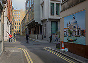 A red-shirted workman carries building materials and a wall picture showing a gondolier and the church of Santa Maria della Salute church in Venice, on 16th March 2017, on the corner of Duke of York Street, in St james's, London, England.