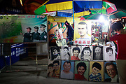 A poster depicting vigilant police officers stands next to a stall advertising hand drawn portraits of Chinese celebrities and David Beckham on the carnival grounds of the Qingdao (Tsingtao) Beer Festival in Qingdao, China on 27 August, 2011. Named after the locally brewed Tsingtao Beer, one of China's most famous exports, the festival has grown from a local binge drinking feast to an internationally known festival.