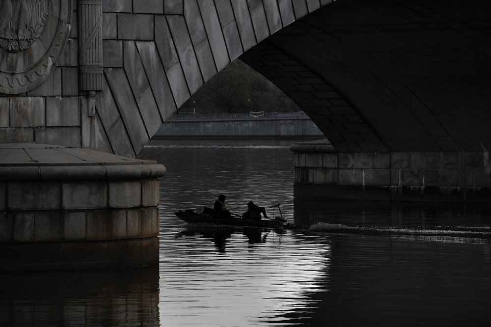 A boat is cast in shadow as it passes beneath the Arlington Memorial Bridge in the early morning hours on the Potomac River in Washington, DC.