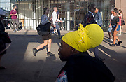 A lady wearing yellow headwear at a bus stop as commuters walk southwards over London Bridge, from the City of London - the capitals financial district founded by the Romans in the 1st century - to Southwark on the south bank, on 2nd August 2018, in London, England.
