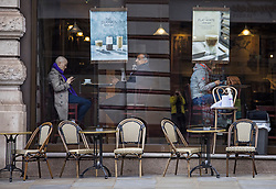 © Licensed to London News Pictures. 17/05/2021. London, UK. Members of the public enjoy coffee while seated inside at a coffee shop in Piccadilly, central London, as seats outside remain empty. From today, lockdown rules are easing with pubs and restaurants able to serve customers indoors, and social distancing guidelines relaxed. Photo credit: Ben Cawthra/LNP