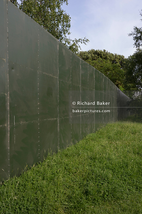 Around the perimeter wall of the Field Day Festival on 1st June 2018, in Brockwell Park, south London borough of Lambeth, England. Highlighting the use of green space for private enterprise has led to protests around the UK, against borough councils handing over public parks otherwise enjoyed by local communities for many weeks before and after the event.