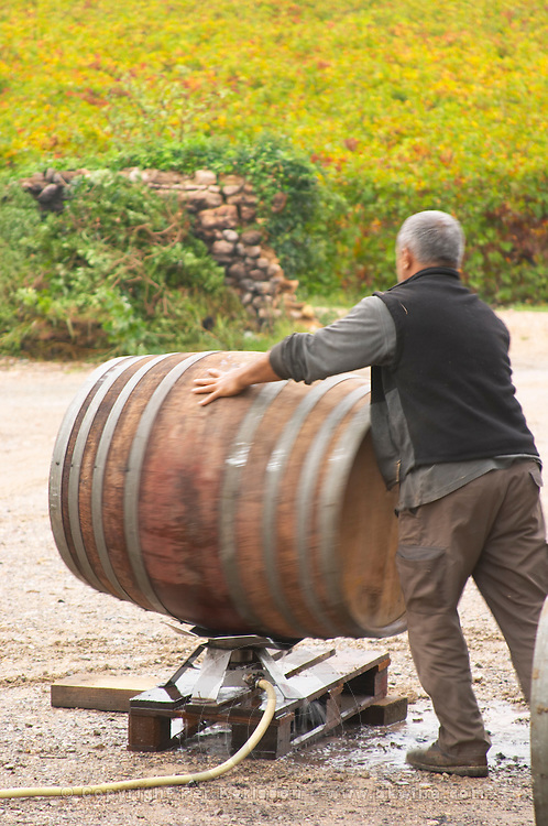 Domaine d'Aupilhac. Montpeyroux. Languedoc. Man cleaning empty barrels with hot water outside the cellar. France. Europe.