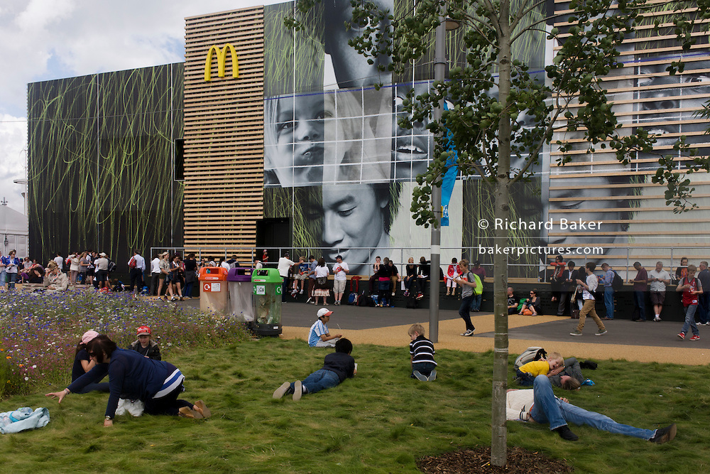 Spectators rest outside the world's biggest McDonald's in the Olympic Park during the London 2012 Olympics. Hundreds of food outlets at Olympic venues have been forced to take chips off the menu, because of a demand from sponsor McDonald's. Olympic chiefs banned all 800 food retailers at the 40 Games venues across Britain from dishing up chips because of 'sponsorship obligations. This land was transformed to become a 2.5 Sq Km sporting complex, once industrial businesses and now the venue of eight venues including the main arena, Aquatics Centre and Velodrome plus the athletes' Olympic Village. After the Olympics, the park is to be known as Queen Elizabeth Olympic Park.