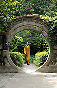 A Buddhist monk walks through a circular gate in Tanzhesi. Situated in the Western Hills, this Buddhist temple lies 45km west of Beijing. The temple name means 'Dragon Pool and Mulberry Tree Temple', due to its proximity to the Dragon Pool and the trees growing in the surrounding hills.