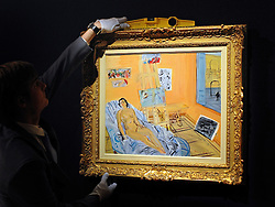 © Licensed to London News Pictures. 02/02/2012, London, UK. A gallery assistant uses a spirit level to hang artist Raoul Dufy's 'Atelier de la rue Jeanne-d'arc, nu couch au passant. The painting is expected to raise 250,000-350,000GBP. Photo call at Bonhams, London for Impressionist and Modern Art Auction preview..  Photo credit : Stephen Simpson/LNP