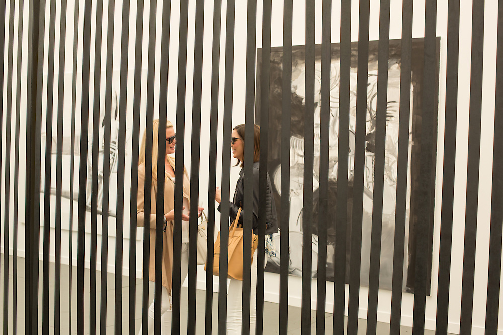 Visitors chat behind the black blinds in the booth of Galerie Gisela, from Cologne.