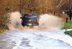 © Licensed to London News Pictures. 04/01/2016. Laddingford, UK. Vehicles struggle through flood water on the main road into the village of Laddingford, Kent, where heavy rain has caused the River Teise to burst it's banks. Photo credit: Grant Falvey/LNP