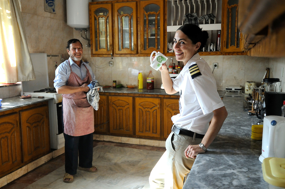 """Pilot, Danielle Aitchison, age 28, with her chef Mr. Flowers at her crew house in Kabul.  Daniel flies in Afghanistan for The United Nations Humanitarian Air Service (UNHAS).   ...When asked about flying in a war zone, she says,  """"I'm just a normal average female.  My job is maybe a little different to some, but I have the same feminine side as other women.  I don't have any trouble going back to New Zealand relating to people.  I'm just a regular chick.""""."""
