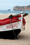Traditional red and white wooden Portuguese fishing boat on the beach of Nazare, Portugal. These boats are on display by the Dry Fish Museum