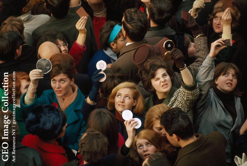 Women use compact mirrors in packed crowd to catch sight of queen.