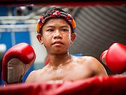 28 JULY 2013 - BANGKOK, THAILAND:  A young boxer gets ready for his bout at the ASEAN Muay Thai Championship at MBK shopping center in Bangkok.      PHOTO BY JACK KURTZ