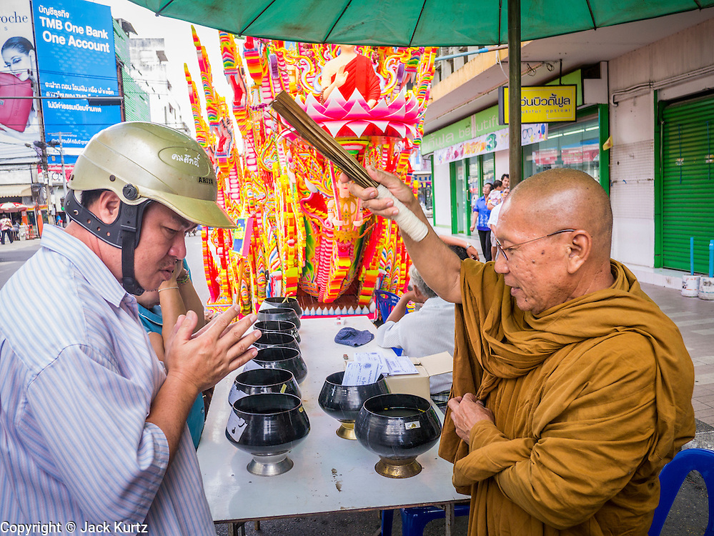 02 NOVEMBER 2012 - HAT YAI, SONGKHLA, THAILAND: A Buddhist monk blesses people in front of an Ok Phansa carriage in Hat Yai, Songkhla, Thailand. Hat Yai is the commercial center of south Thailand and a popular weekend vacation destination for Malaysian and Singaporean tourists.    PHOTO BY JACK KURTZ