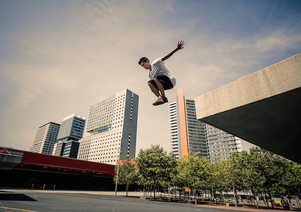 Young man practicing parkour in the city of Barcelona