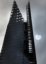 © Licensed to London News Pictures. 10/06/2021. London, UK. The moon passes in front of the sun during a partial eclipse viewed next to The Shard in central London. Photo credit: Peter Macdiarmid/LNP