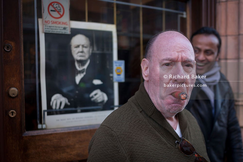 A cigar smoking aficionado inhales in front of a portrait of Winston Churchill, outside Sautter Cigars, on 20th January 2017, in Mount Streeet, Mayfair, London, England.